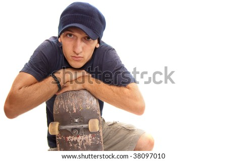 skater posing with his board, resting on one knee - stock photo