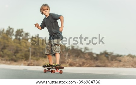 Skater  riding on the road at sunset - stock photo