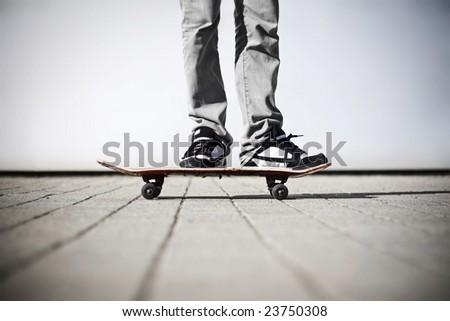 skater standing on his skateboard - stock photo