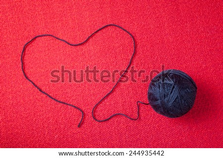 skein of black thread on a red background - stock photo