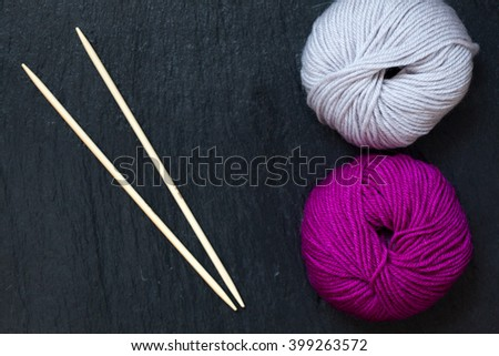 skein of pink and grey yarn with bamboo knitting needles with black slate background