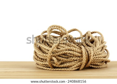 Skein of synthetic rope lies on a wooden countertop on a white background - stock photo