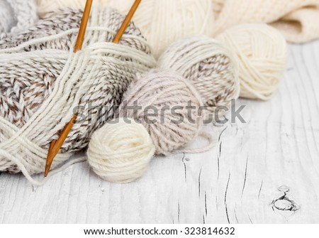 Skeins of wool and knitting needles from bamboo on a wooden background - stock photo