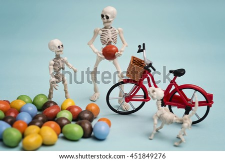 Skeleton and his skeleton kid and their dog getting chocolate candy with bicycle - stock photo