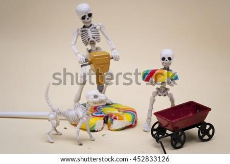 Skeleton and skeleton kid hauling lollipop - stock photo