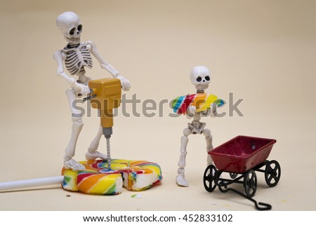 Skeleton breaking lollipop into pieces  - stock photo