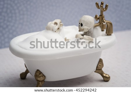 Skeleton dog and skeleton kid getting bubble bath