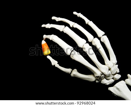 skeleton hand holding a piece of candy corn isolated on a black background - stock photo
