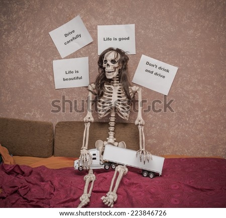 skeleton in a wig sitting on the bed,with truck and trailer model on his legs, leaning against the wall with various messages about safety and driving behavior on the road - stock photo
