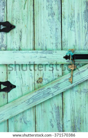 Skeleton key with Love hanging from rope on antique mint green rustic wood door - stock photo