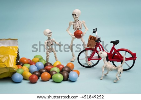 Skeleton kid and skeleton getting chocolate candy - stock photo