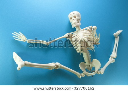 Skeleton model action on blue background. - stock photo