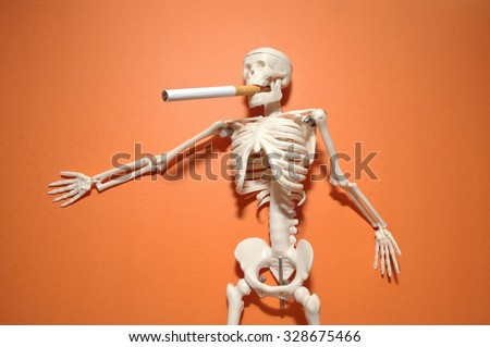 skeleton model action smoking on oren color background - stock photo