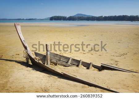 Skeleton of destroyed boat in area of sea tide - stock photo