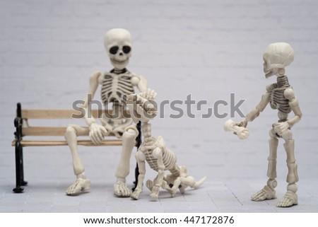 skeleton petting his skeleton dog while little skeleton offering bone - stock photo