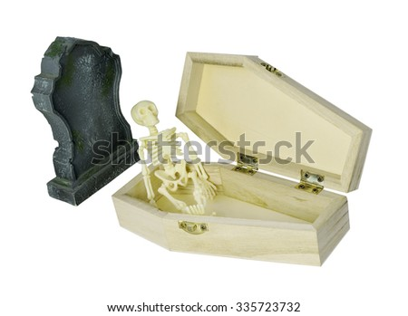 Skeleton sitting in coffin next to gravestone - path included - stock photo