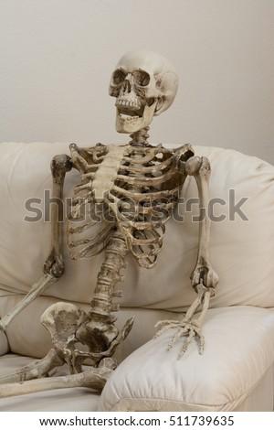 skeleton sitting white chair against white stock photo