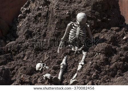 Skeleton sitting on the ground. - stock photo