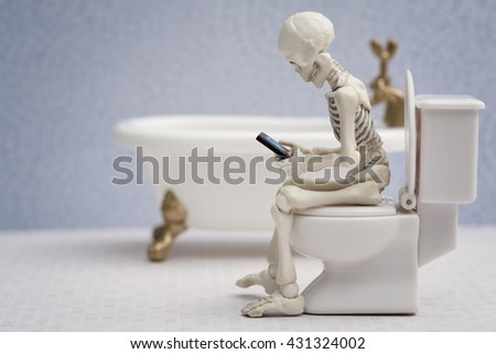 Skeleton sitting on water closet a smartphone in his hand