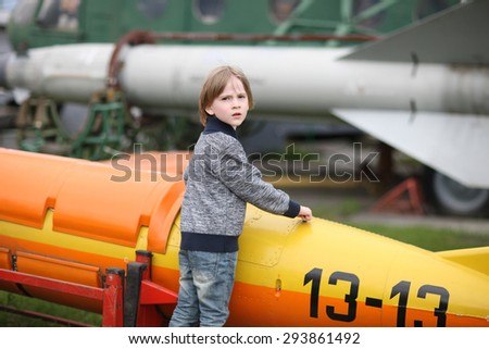 Skeptical face of an elementary-aged boy examining a vintage aircraft - stock photo