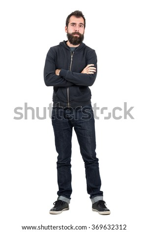 Skeptical hipster in black hooded sweatshirt with crossed arms looking at camera. Full body length portrait isolated over white studio background.  - stock photo