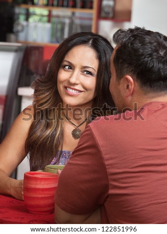Skeptical Hispanic woman listening to man talk in cafe - stock photo