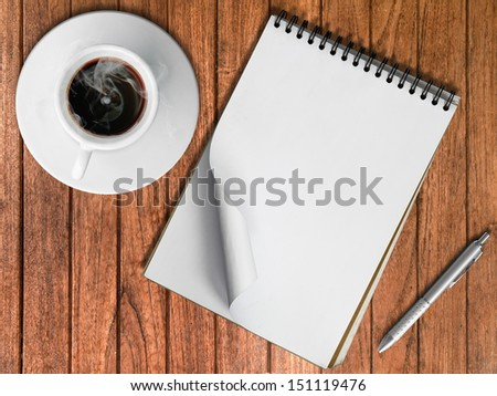 Sketch book Silver pen and White cup of hot coffee on wood table - stock photo