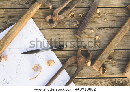 Sketch, pencil and old rusty tools on wooden table - stock photo