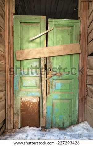 Skewed old green door in wooden house. Torn lock, clogged entrance. Dirty snow in from of building. Winter in city.