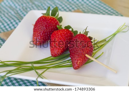 Skewer with three strawberries over green stems, on white plate and tablecloth colors