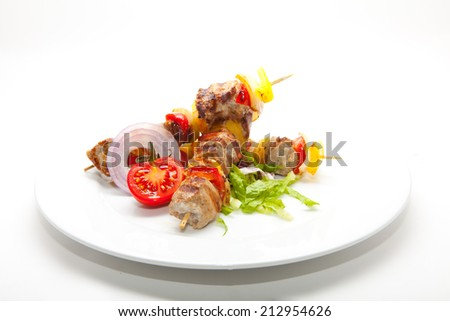 Skewered on wooden sticks tasty pork meat and vegetables mix, grilled meat  on a white background
