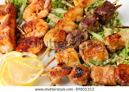 skewers of different meats on a wooden sticks on a white platter with lemon - stock photo