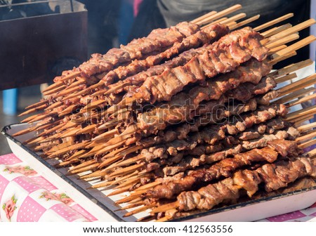 skewers of meat prepares outdoors - stock photo