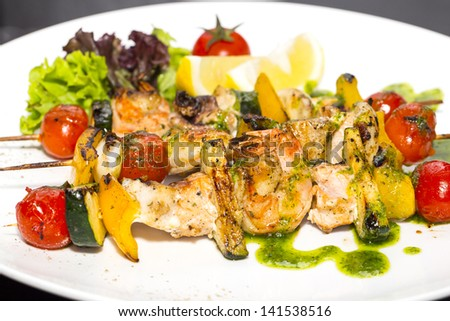 skewers of seafood grilling - stock photo