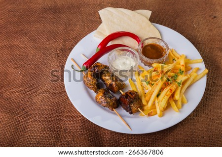 Skewers with french fries. Skewers of meat. Eastern food. - stock photo