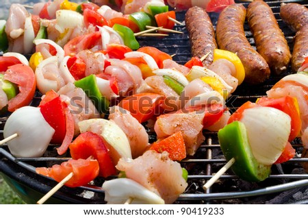 Skewers with meats and vegetables cooking on the grill