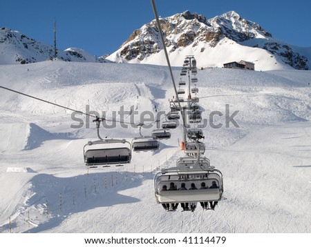 Ski chair-lift with skiers (Switzerland) - stock photo