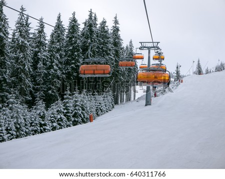 Ski chair lift with skiers view from next chair.