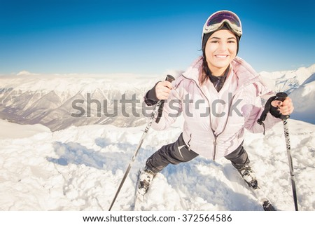 Ski. Happy female skier on the background of high snow-capped Alps in Swiss - stock photo