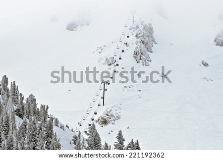 Ski lift chair ascending the mountainside - stock photo