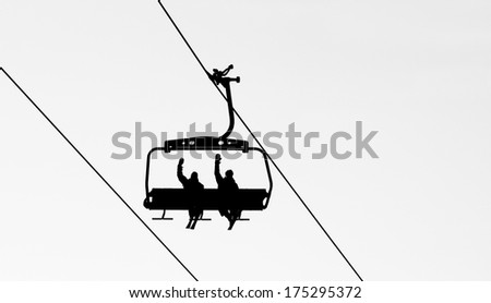 Ski lift chairs on bright winter day over the clouds black and white - stock photo