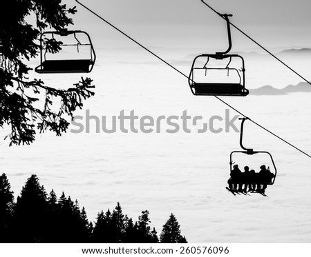 Ski lift chairs on bright winter day over the clouds, cableway funicular chair equipment, Austria - stock photo