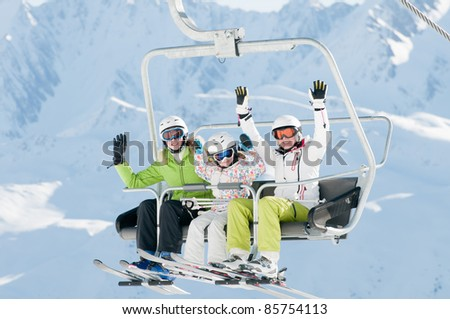 Ski lift - happy skiers in ski resort - stock photo