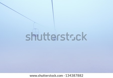 ski-lift in fog in front of mountain - stock photo