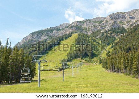 Ski lift in the Canadian Rocky Mountains in summer - stock photo