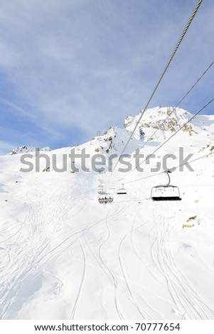 Ski lift in winter snow mountain landscape with blue cloudy sky. Alps. France. - stock photo