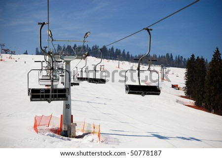 Ski lift with seating bench. Slope underneath.