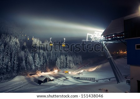 Ski lifts (gondolas) at night - stock photo