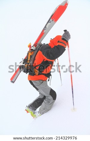 Ski mountaineer ascending on snow covered trail in bad weather - stock photo