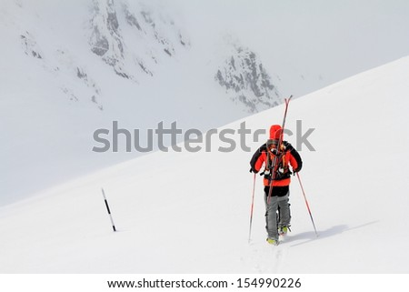 Ski mountaineer ascending the mountain in bad weather - stock photo